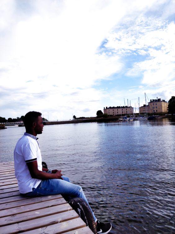 Abdirahman Jamal istuu järven rannalla.