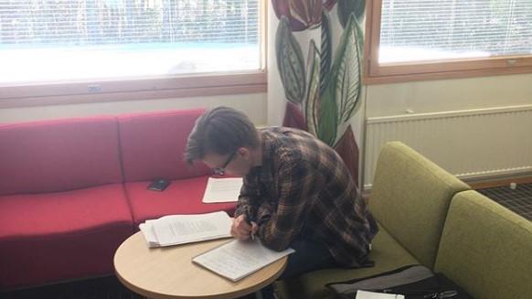 Tuomas Läspä istuu pöydän ääressä ja lukee papereita.