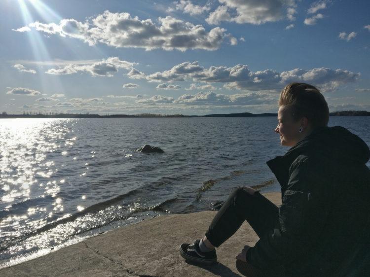 Vera Kettunen istuu järven rannalla.