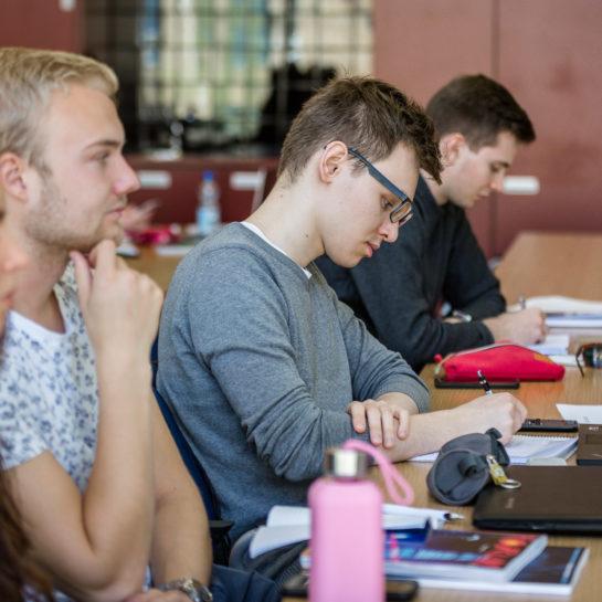 Opiskelijoita oppitunnilla istumassa ja kuuntelemassa.