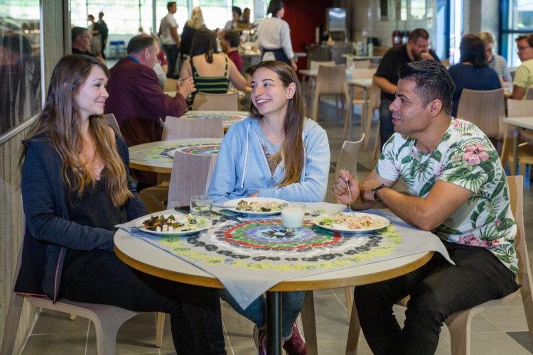 Kolme opiskelijaa istuu opiston ruokalassa, ruokailee ja keskustelee.
