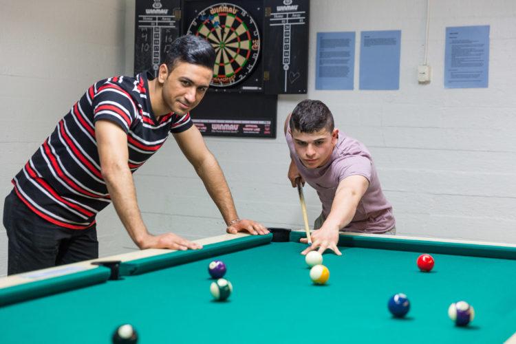 Kaksi opiskelijanuorukaista pelaa biljardia.