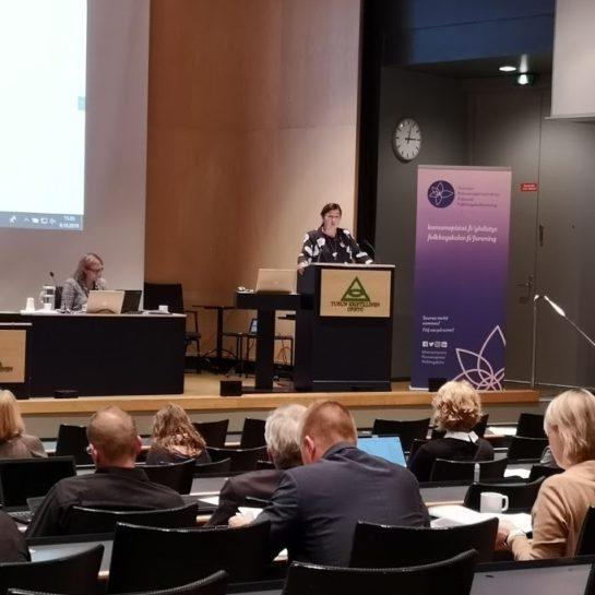 Helena Ahonen puhumassa auditoriossa puhujanpöntön takana.