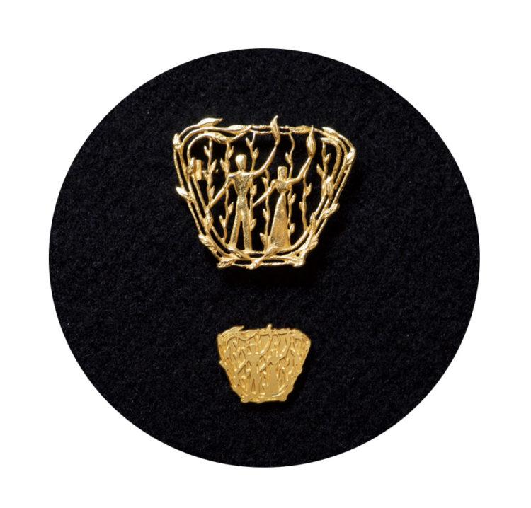 Kultainen ansiomerkki ja siihen kuuluva pinssi.