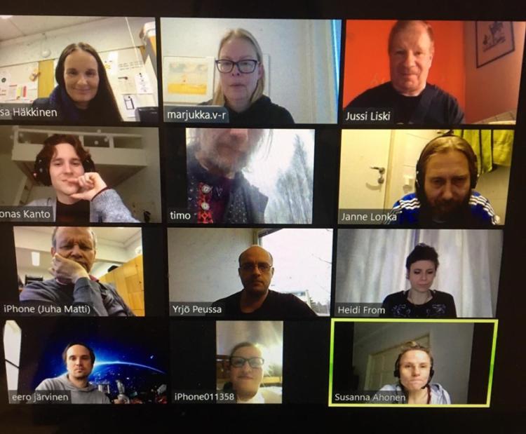 Tietokoneen kuvalla oleva näyttökuva etäkokouksesta, jossa monen osallistujan kasvot.